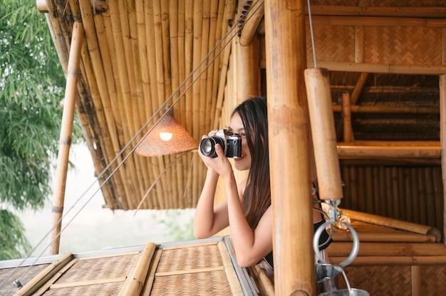 Atrakcyjna azjatycka kobieta robi zdjęcie aparatem retro przez okno w kurorcie z drewnianą chatą