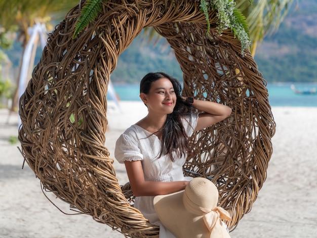 Atrakcyjna azjatycka kobieta siedzi na drewnianym owalnym gnieździe na białej, piaszczystej plaży, patrząc na widok na morze i uśmiechając się
