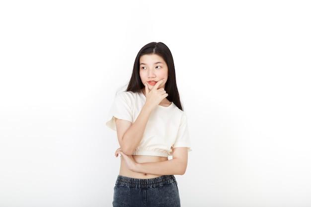 Atrakcyjna azjatycka kobieta w neutralnym myśleniu stojącym dorywczo strój