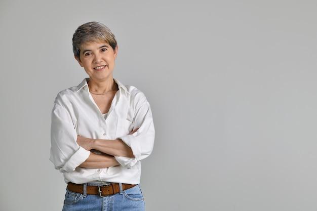 Atrakcyjna azjatycka kobieta w średnim wieku z założonymi rękami na białym tle