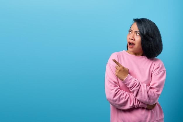 Atrakcyjna azjatycka kobieta zszokowana i wskazująca palcem na pustą przestrzeń na niebieskim tle