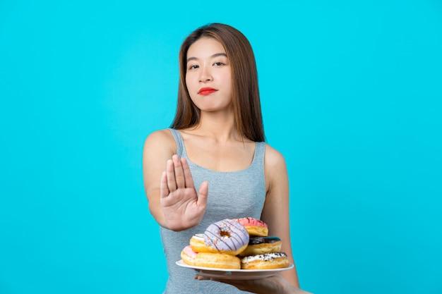 Atrakcyjna azjatycka młoda kobieta nie robi żadnej akcji z pączkami na odosobnionej błękitnej kolor ścianie
