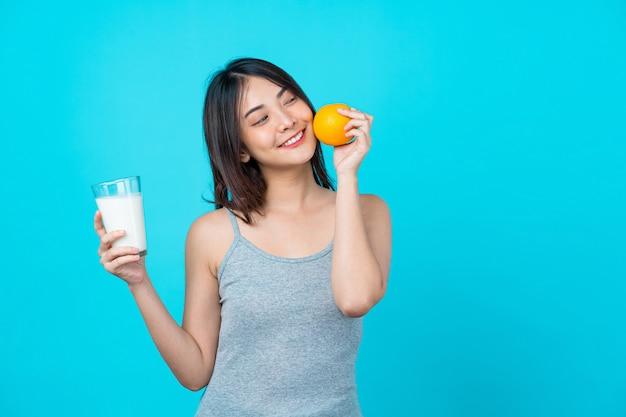 Atrakcyjna azjatycka młoda kobieta trzyma i wybiera między mlekiem i pomarańcze na odosobnionej błękitnej kolor ścianie