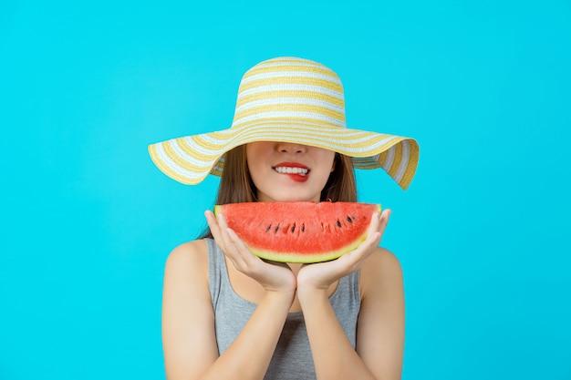Atrakcyjna azjatycka młoda kobieta w letnim kapeluszu i trzymająca zjeżdżalnię z arbuza na izolowanej niebieskiej ścianie, seksowne gryzienie ust, kopia przestrzeń i studio, moda podróż i koncepcja turystyczna