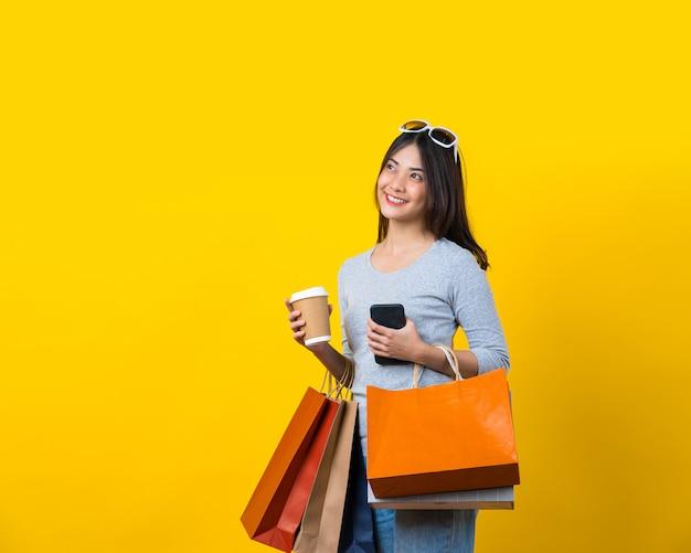 Atrakcyjna azjatycka uśmiechnięta młoda kobieta niesie zakupy coloful torbę, telefon komórkowego i papierową filiżankę kawy na aisolated żółtej ścianie