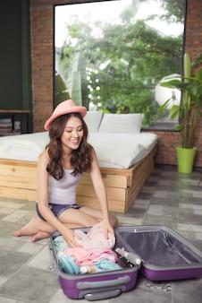 Atrakcyjna azjatykcia młoda kobieta pakuje torbę podróżną przed wyjazdem na wakacje. koncepcja stylu życia.