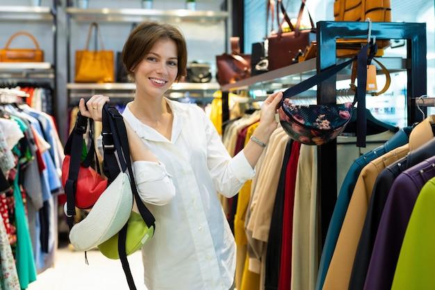 Atrakcyjna biała kobieta trzyma w rękach wiele torebek