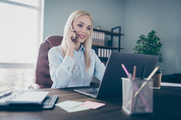 Atrakcyjna biznesowa dama rozmawiająca z kolegami rozmawia przez telefon