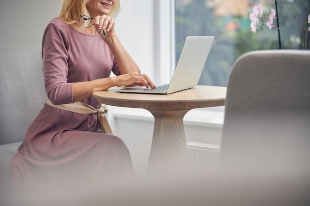 Atrakcyjna biznesowa dama trzymająca uśmiech na twarzy, patrząc na ekran swojego laptopa