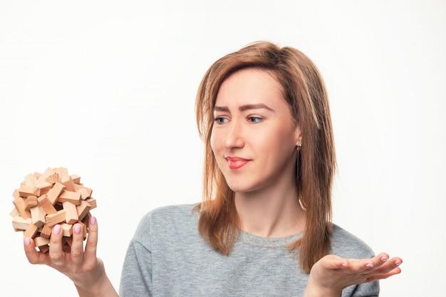 Atrakcyjna biznesowa kobieta patrzeje wprawiać w zakłopotanie z drewnianą łamigłówką