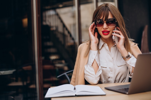 Atrakcyjna biznesowa kobieta pracuje na komputerze w kawiarni