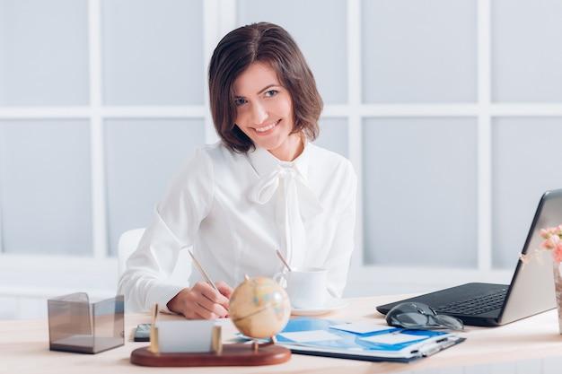 Atrakcyjna biznesowa kobieta pracuje przy biurku w biurze