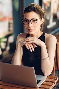 Atrakcyjna biznesowa kobieta pracuje przy jego laptopem