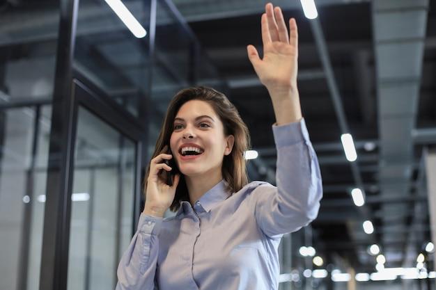 Atrakcyjna biznesowa kobieta rozmawia przez smartfon i macha ręką, witając cię.