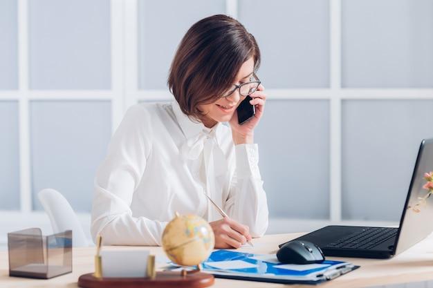 Atrakcyjna biznesowa kobieta rozmawia przez telefon i pracuje przy biurku w biurze