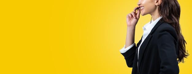 Atrakcyjna biznesowa kobieta w garniturach i słuchawkach uśmiecha się podczas pracy