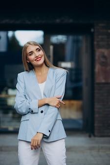 Atrakcyjna biznesowa kobieta w niebieskiej marynarce przy centrum biurowym