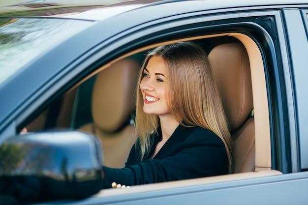 Atrakcyjna biznesowa kobieta z okulary uśmiecha się jej samochód i jedzie.