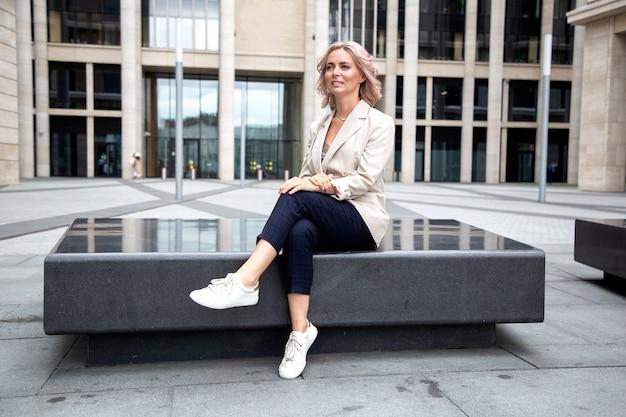 Atrakcyjna bizneswoman pozuje na tle w centrum biznesowym