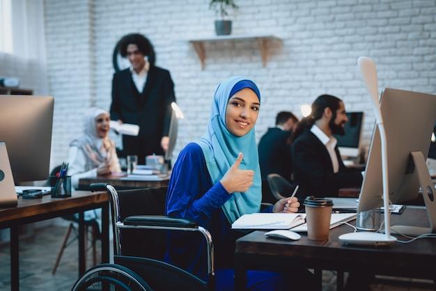 Atrakcyjna bizneswoman w hidżabie przy stacją roboczą.