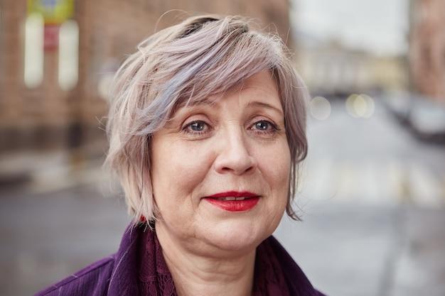 Atrakcyjna bizneswoman w średnim wieku z krótkimi włosami farbowanymi pozuje na ulicy miasta.