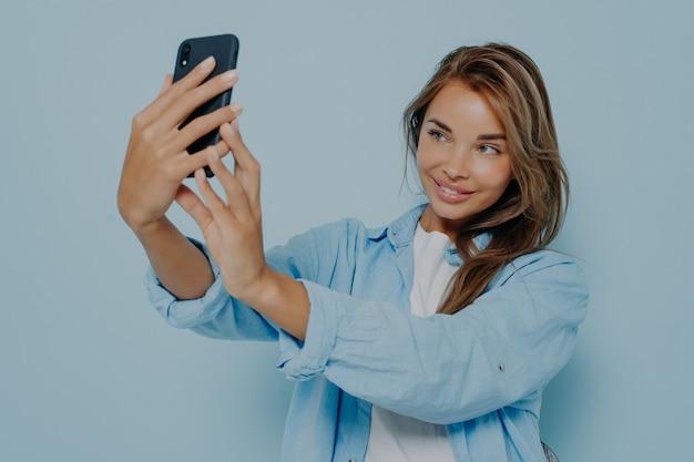 Atrakcyjna blogerka trzymająca nowoczesny smartfon i robiąca selfie, transmitująca lub filmująca wideo dla mediów społecznościowych, pozytywnie uśmiechająca się do kamery podczas pozowania na niebieskiej ścianie. ludzie i technologie