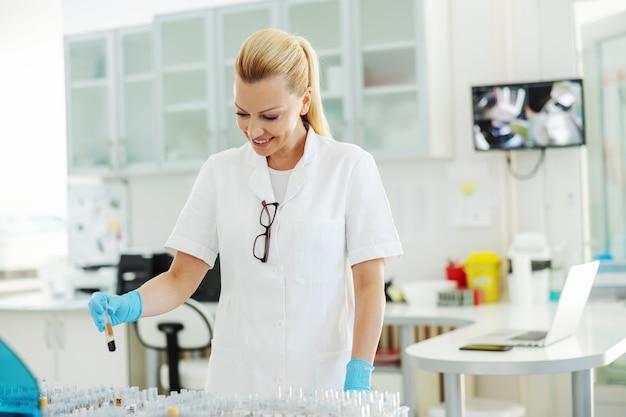 Atrakcyjna blond asystentka laboratoryjna w białym sterylnym mundurze, w ochronnych gumowych rękawiczkach, trzymająca probówkę z próbką krwi.