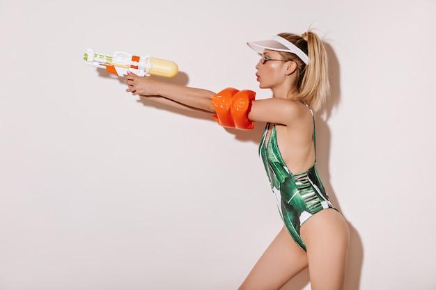 Atrakcyjna blond dama w okularach, czapce i zielonym fajnym stroju kąpielowym pozuje z pistoletem na wodę na izolowanej białej ścianie