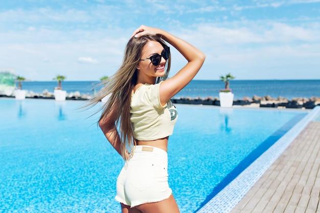 Atrakcyjna blond dziewczyna z długimi włosami stoi w pobliżu basenu. trzyma rękę na głowie. widok z tyłu.