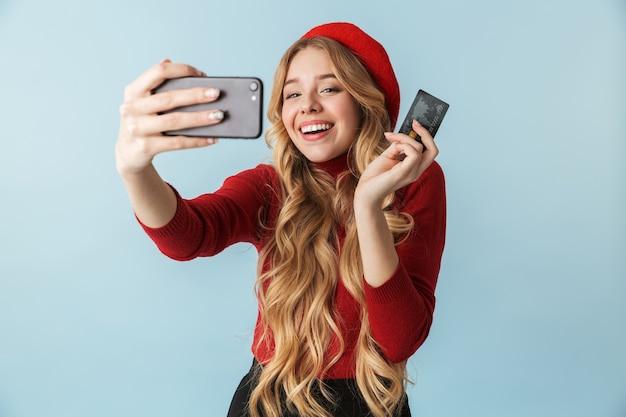 Atrakcyjna blond kobieta 20s trzymając kartę kredytową podczas robienia zdjęcia selfie na telefon komórkowy na białym tle