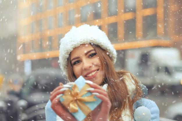 Atrakcyjna blond kobieta nosi białą czapkę z dzianiny i trzyma niebieskie pudełko prezentowe, spacerując po mieście podczas opadów śniegu