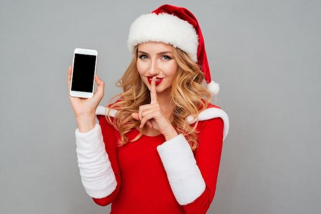 Atrakcyjna blond kobieta w sukience świętego mikołaja i czerwonym kapeluszu trzymająca pusty ekran telefonu komórkowego i pokazująca gest ciszy na szarej powierzchni