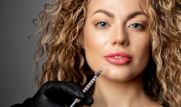 Atrakcyjna blond kobieta z kręconymi włosami o zastrzyk powiększania ust w gabinecie kosmetycznym. strzał zbliżeniowy