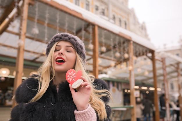 Atrakcyjna blond modelka z zamkniętymi oczami trzymająca smaczne piernikowe ciastko w świetle dekoracji na placu w kijowie