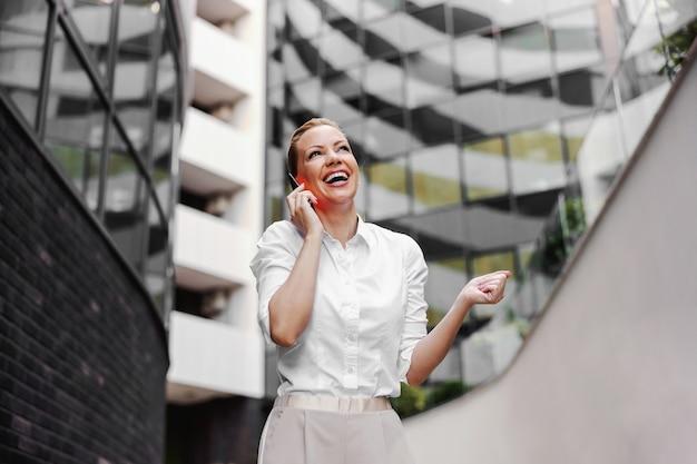 Atrakcyjna blond modna bizneswoman rozmawia przez telefon na zewnątrz centrum biznesowego.