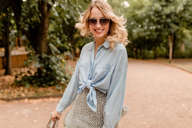 Atrakcyjna blond szczera kobieta spaceru w parku w stylowym stroju na sobie eleganckie okulary przeciwsłoneczne i torebkę