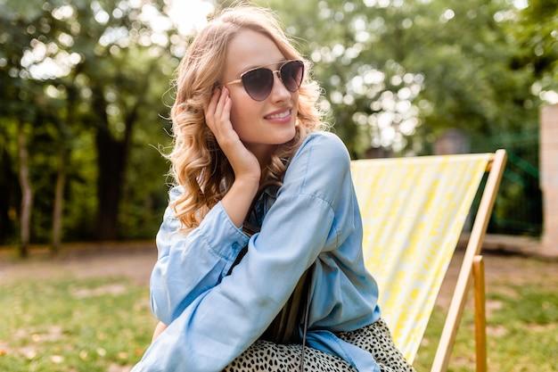 Atrakcyjna blond uśmiechnięta kobieta siedzi w leżaku w letnim stroju