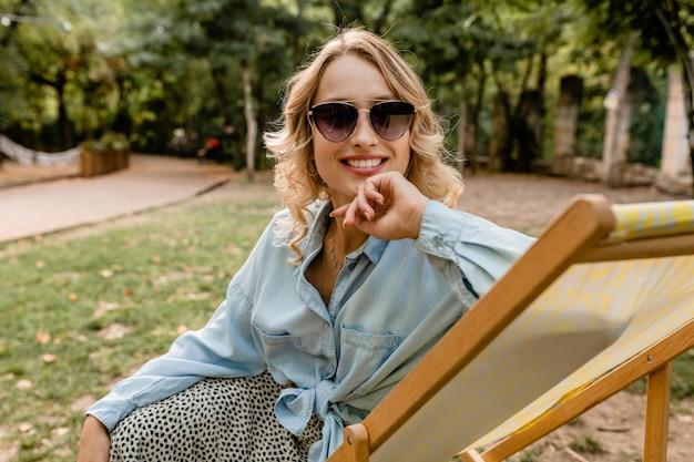 Atrakcyjna blond uśmiechnięta kobieta siedzi zrelaksowany w leżaku w stylowy strój