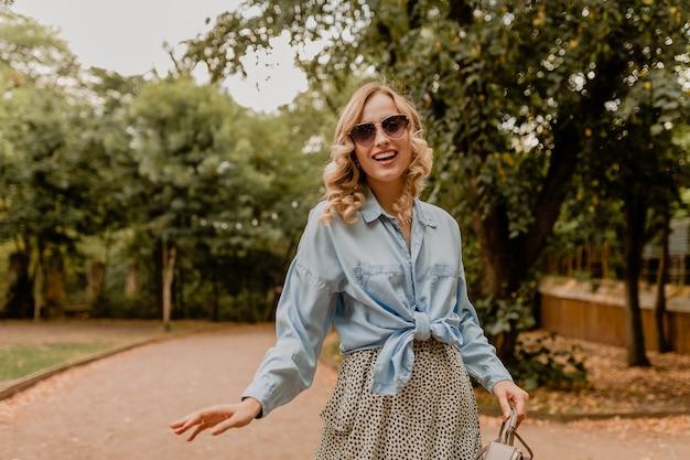 Atrakcyjna blond uśmiechnięta kobieta spaceru w parku w stylowym stroju