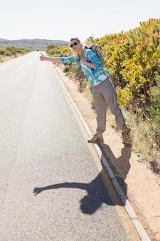 Atrakcyjna blondynka autostop turystyka na wiejskiej drodze w słoneczny dzień