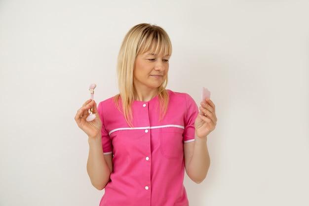Atrakcyjna blondynka kosmetolog trzyma w dłoniach przyrządy kosmetyczne do chińskiego masażu gua sha. młodość i piękno. salony piękności. kosmetyka. dermatologia. zabiegi kosmetyczne. narzędzia kosmetyczki.