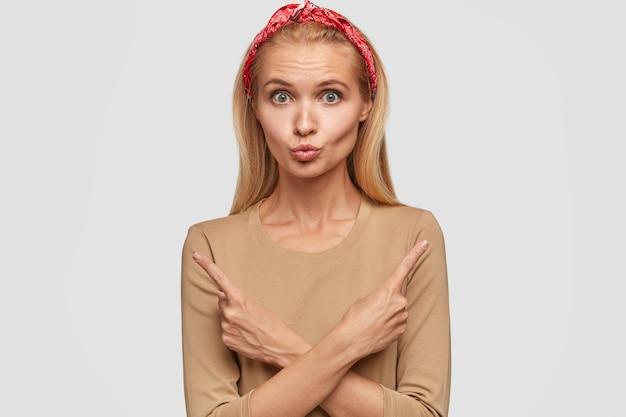 Atrakcyjna blondynka młoda kobieta pozuje na białej ścianie