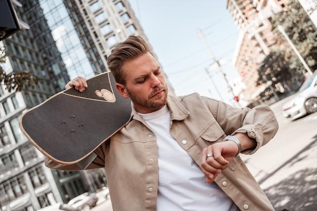 Atrakcyjna blondynka młody człowiek deskorolkarz trzymając longboard na ramieniu w pośpiechu, patrząc poważnie na zegarek. w ruchu miejskim tle budynku. nosi beżową dżinsową koszulę. wypoczynek na świeżym powietrzu. dojeżdżać