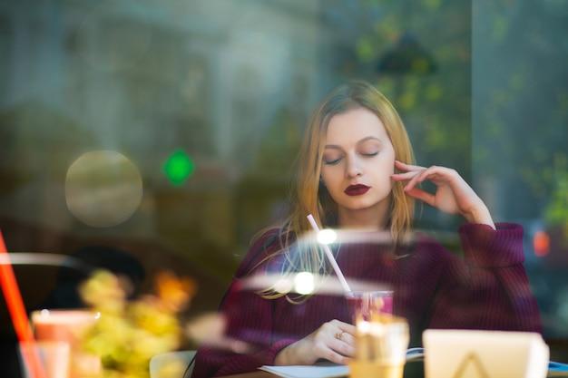 Atrakcyjna blondynka modelka spędzająca czas w restauracji przy filiżance koktajli. strzał przez szybę w oknie. pusta przestrzeń