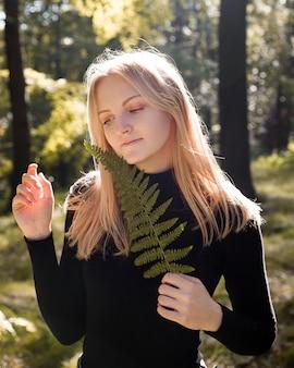 Atrakcyjna blondynka, patrząc w dół i trzymając liść paproci, fotografia artystyczna