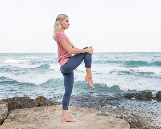 Atrakcyjna blondynka robi joga na świeżym powietrzu