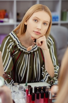 Atrakcyjna blondynka siedzi przed lustrem, myśląc o swoim wyglądzie