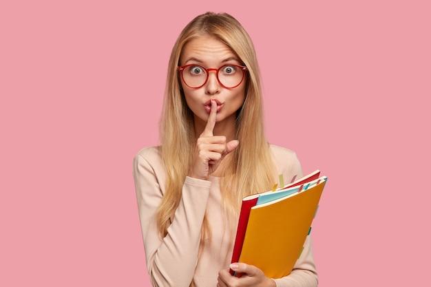 Atrakcyjna blondynka studentka pozuje na różowej ścianie