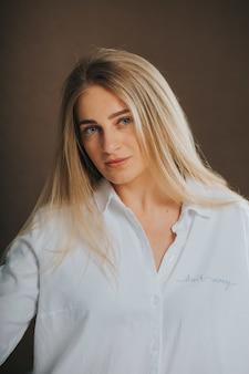 Atrakcyjna blondynka w białej koszuli pozuje na brązowej ścianie