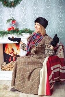 Atrakcyjna blondynka w brązowej sukience i czarnym futrzanym kapeluszu w pobliżu choinki i kominka